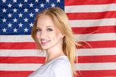 Young blonde girl posing against american flag — Stock Photo