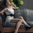 Beautiful woman seated on a sofa — Stock Photo