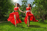 Two young happy beautiful women running on grass — Stock Photo