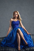 Young woman in luxurious blue dress — Stock Photo