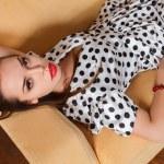Beautiful woman seated on a sofa — Stock Photo #30971673