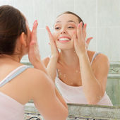 Young woman washing her face with clean water — Stock Photo