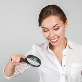 Attractive woman looking through a magnifying glass — Foto Stock