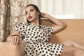 Piękna kobieta siedzi na kanapie — Zdjęcie stockowe