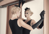 Elegant woman looking at herself in the mirror — Stock Photo