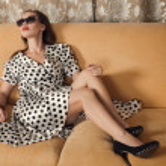 Beautiful woman seated on a sofa — Stock Photo #31829091