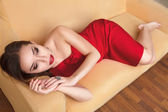 Young woman sitting on sofa — Stock Photo