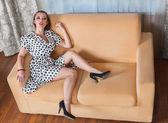Mujer joven sentada en el sofá — Foto de Stock