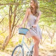 Stock Photo: Young woman with retro bicycle in a park