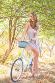 Young woman with retro bicycle in a park — Stock Photo