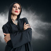 Young woman in black hood with cross — Stock Photo
