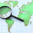 Stock Photo: Magnifying glass black frame on world map paper.