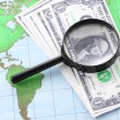 Stock Photo: Magnifying glass black frame and currency on world map paper.