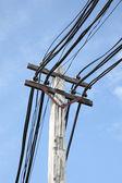 Elektrický kabel na pólu v modré obloze. — Stock fotografie
