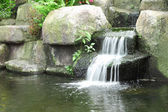 Small waterfall in public tropical garden. — Stock Photo