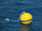 Yellow buoy floating on blue sea. — Stock Photo