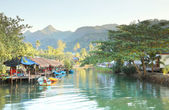 Tropical fishing house villager canal and some boat near mountain. — Stock Photo