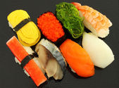 Several type sushi food on black plate. — Stockfoto