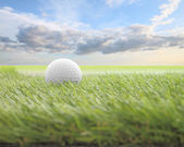 Golf ball on green front of blur cloud morning sky. — Stock Photo