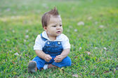 Cute baby sitting in the grass — Stock Photo