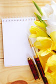 Notebook,pen and flowers on wooden background — Stock Photo