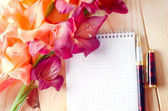 Notebook and flowers on wooden background — Stock Photo
