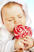 Little girl with sweet color candy — Stock Photo