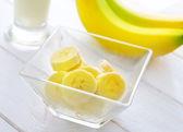 Fresh banana in the glass bowl, banana and milk — Stock Photo