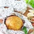 Baked potato in foil - Stock Photo