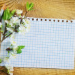 Flowers and note on wooden background — Stock Photo