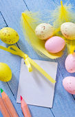 Colored quail eggs with paper for message — Stock Photo
