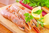 Shrimp with lemon wedges — Stock Photo