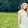 Beautiful blond girl on green field with flowers. Rural scene — Stock fotografie