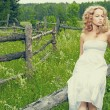 Beautiful blond girl on green field with flowers. Rural scene — Stock Photo