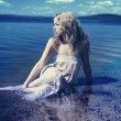Young sexy blond woman in the blue water in wet white dress — Stock Photo #17462313