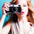 Beautiful blond photographer woman holding retro camera — Stock Photo #17465247