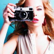 Beautiful blond photographer woman holding retro camera - Stock Photo