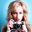 Beautiful blond photographer woman holding retro camera — Stock Photo