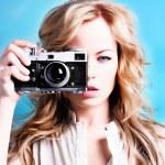 Beautiful blond photographer woman holding retro camera — Stock Photo