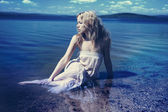 Young sexy blond woman in the blue water in wet white dress — Stock Photo