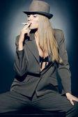 Beautiful smoking girl in hat — Stock Photo