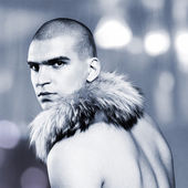 Handsome muscular young man with fox fur collar — Stock Photo