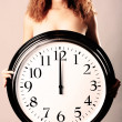 Beautiful girl with a wall clock - Stockfoto