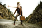 Girl hitchhiking with suitcase — Stock Photo