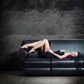 The beautiful woman lying on a leather sofa — Stock Photo