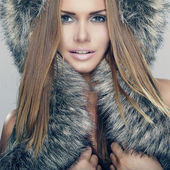 Fashion portrait of young pretty woman with fur — Stock Photo