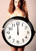 Hermosa chica con un reloj de pared — Foto de Stock