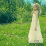 Beautiful blonde woman on grass in white dress — Stock Photo #18463785