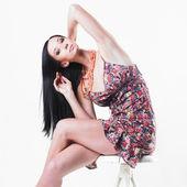 美丽的女人坐在白色椅子上的肖像 — 图库照片