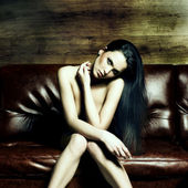 Portrait of a beautiful naked young woman on a leather sofa — Stock Photo